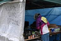 """A makeshift kitchen, with a sign that reads, """"Fuel donations accepted,"""" offers free food donated by charities and neighbors at a Montreal homeless camp set up in the summer of 2020"""