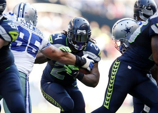 CORRECTS TO RUNS FOR YARDAGE NOT SCORES - Seattle Seahawks' Marshawn Lynch (24) pushes aside Dallas Cowboys' Sean Lissemore as he runs for yardage in the second half of an NFL football game of Sunday, Sept. 16, 2012, in Seattle. (AP Photo/Kevin P. Casey)