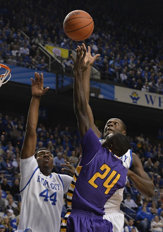 Kentucky's Dakari Johnson, left, and Julius Randle, rear, attempt to block the shot of Montevallo's Ed'Lexus Collier during the first half of an exhibition NCAA basketball game, Friday, Nov. 4, 2013, in Lexington, Ky. (AP Photo/Timothy D. Easley)