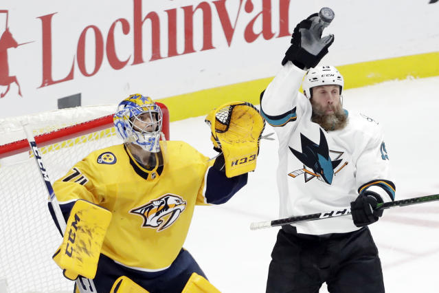 San Jose Sharks center Joe Thornton (19) reaches for the puck in front of Nashville Predators goaltender Juuse Saros (74), of Finland, in the third period of an NHL hockey game Tuesday, Dec. 10, 2019, in Nashville, Tenn. The Predators won 3-1. (AP Photo/Mark Humphrey)