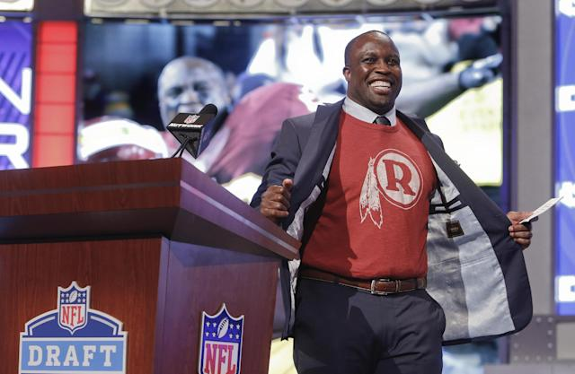 Former Washington Redskins linebacker London Fletcher flashes a Redskins shirt under his jacket before announcing Stanford's Trent Murphy as the 47th selection by the Redskins for the second round of the 2014 NFL Draft, Friday, May 9, 2014, in New York. (AP Photo/Jason DeCrow)