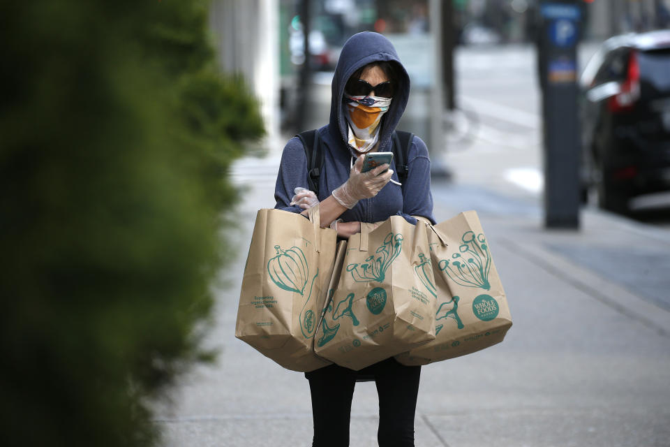 NEW YORK NY, - APRIL 12: A woman with groceries looks at her portable telephone while wearing protective gloves and a homemade mask amid the coronavirus pandemic on April 12, 2020 in New York City. COVID-19 has spread to most countries around the world, claiming over 114,000 lives with infections at over 1.8 million people. (Photo by John Lamparski/Getty Images)
