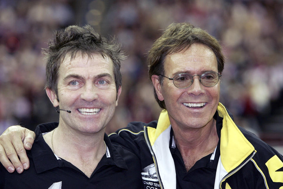 "BIRMINGHAM, ENGLAND - DECEMBER 18: Sir Cliff Richard and actor Bradley Walsh take part in the ""Intelligent Finance Cliff Richard Tennis Classic"" at Birmingham National Indoor Arena on December 18, 2004 in Birmingham, England. The annual tournament raises money for the Cliff Richard Tennis Foundation, which introduces children across the country to the game. (Photo by MJ Kim/Getty Images)"