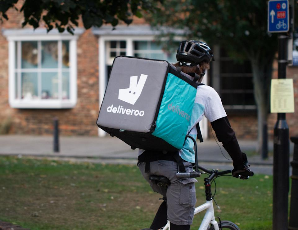 York, UK - September 28, 2016.A cyclist from the increasingly popular take away delivery company Deliveroo speeding through city streets with a hot food delivery from take aways and restaurants to homes.