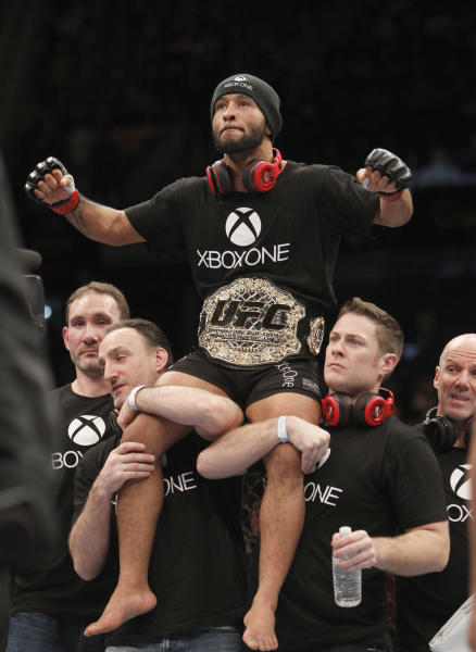 Defending champ Demetrious Johnson, top, celebrates with his crew after knocking out Joseph Benavidez in a UFC flyweight mixed martial arts title fight in Sacramento, Calif., Saturday, Dec. 14, 2013. (AP Photo/Steve Yeater)