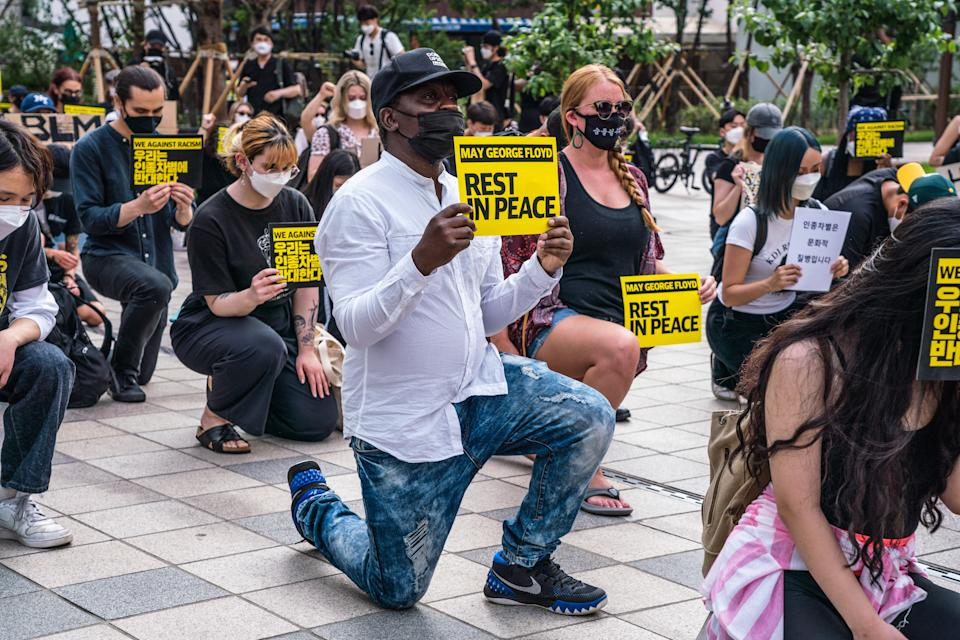 SEOUL, SOUTH KOREA - 2020/06/06: Protesters wearing protective masks kneel and hold 'May George Floyd Rest In Peace' and 'We Against Racism' placards during the demonstration. Thousands in Seoul support U.S. protests against police brutality that caused the May 25th murder of George Floyd in Minneapolis. (Photo by Simon Shin/SOPA Images/LightRocket via Getty Images)