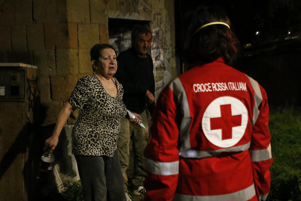 Red Cross volunteers bring food and disinfectants to homeless at Verano cemetery in Rome Saturday, March 21, 2020. For most people, the new coronavirus causes only mild or moderate symptoms. For some it can cause more severe illness. (Cecilia Fabiano/LaPresse via AP)