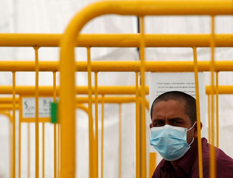 FILE PHOTO: A migrant worker looks on from a swab isolation facility as he waits for his test results at a dormitory, amid the coronavirus disease (COVID-19) outbreak in Singapore