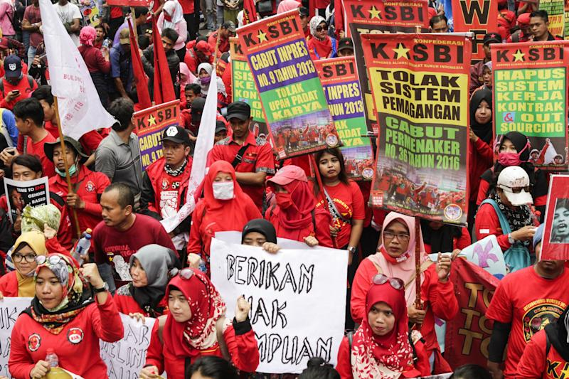 Indonesians hold placards during a rally, organized by several women's organizations, to commemorate International Women's Day.