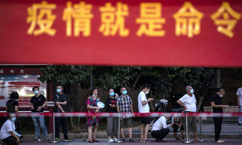 """Residents line up for Covid-19 tests near a banner with the words """"Epidemic is the Order"""" in Wuhan in central China's Hubei province"""