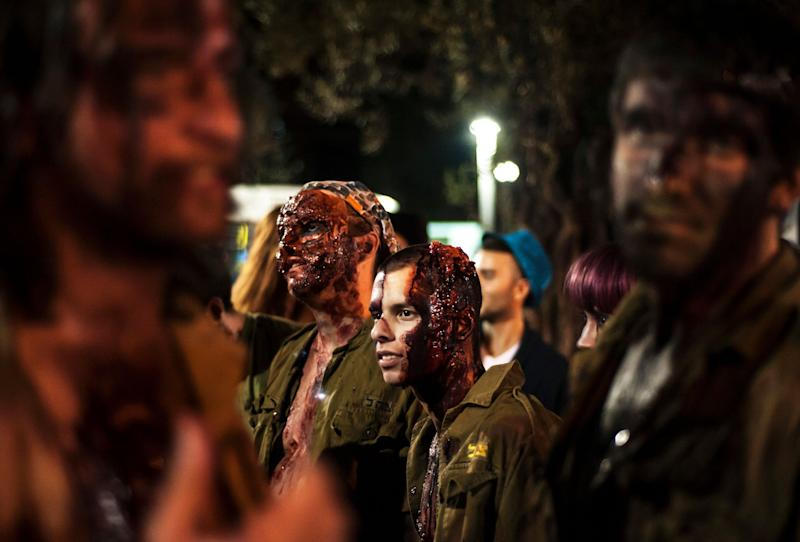Israelis dressed as a zombies takes part in the customary 'Zombie Walk' in the city of Tel Aviv, on the eve of the Jewish holiday of Purim, late on March 15, 2014. The carnival-like Purim holiday is celebrated with parades and costume parties to commemorate the deliverance of the Jewish people from a plot to exterminate them in the ancient Persian empire 2,500 years ago, as described in the Book of Esther. AFP PHOTO/DAVID BUIMOVITCH (Photo credit should read DAVID BUIMOVITCH/AFP/Getty Images)