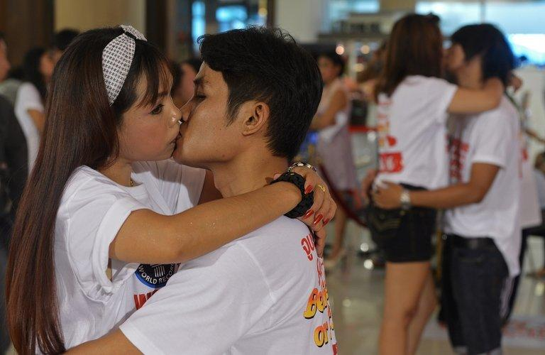 "Thai couples kiss during a competition for the ""World's Longest Continous Kiss"" ahead of Valentine's Day in Pattaya on February 12, 2013. Nine couples took part in the kissing marathon in the hope of breaking the Guinness world record, and in the process to receive prizes totalling more than 200,000 Thai baht (6,700 USD) and a diamond ring"