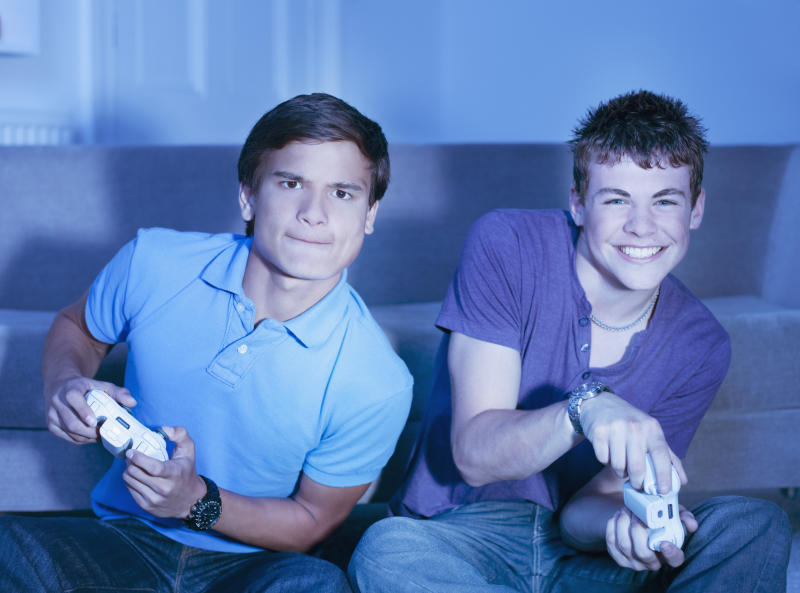 Two boys playing console video games.