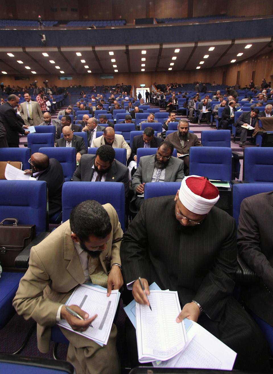 Egyptian lawmakers vote during a session to select a constitutional panel in Cairo, Egypt, Saturday, March 24, 2012. Egyptian parliamentarians on Saturday cast ballots to select a 100-member panel that will draft the country's new constitution, amid deep polarization between liberals and Islamists over the process. (AP Photo/Ahmed Gomaa)