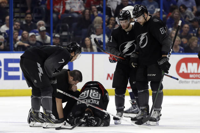 Tampa Bay Lightning trainer Tom Mulligan attends to right wing Nikita Kucherov (86) who was injured during the second period of an NHL hockey game against the Washington Capitals, Saturday, Dec. 14, 2019, in Tampa, Fla. Lightning right wing Mathieu Joseph (7), center Brayden Point (21) and defenseman Erik Cernak (81) look on. (AP Photo/Chris O'Meara)