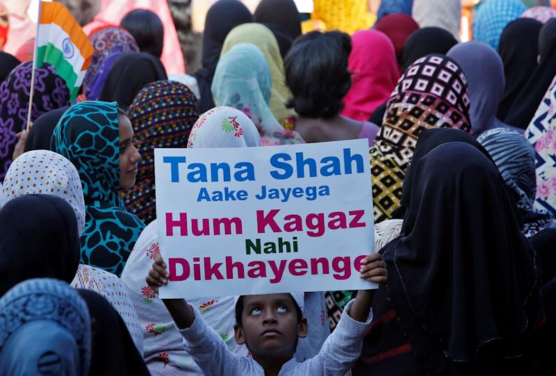 A boy holds up a placard as he attends a protest rally against a new citizenship law, after Friday prayers in Chennai