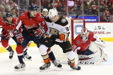 Dec 16, 2017; Washington, DC, USA; Washington Capitals defenseman Dmitry Orlov (9) and Anaheim Ducks right wing Jakob Silfverberg (33) battle for the puck in front of Washington Capitals goalie Braden Holtby (70) in the second period at Capital One Arena. The Capitals won 3-2 in overtime. Mandatory Credit: Geoff Burke-USA TODAY Sports