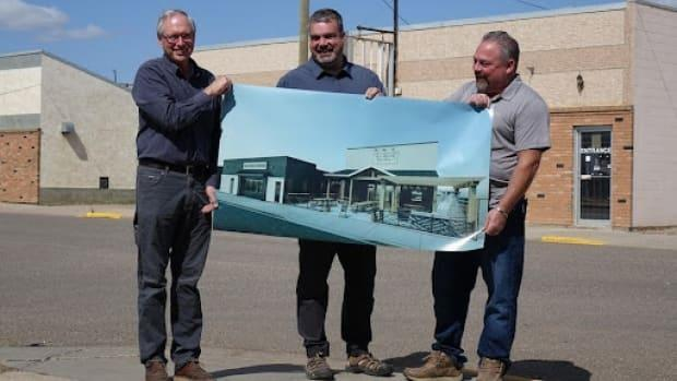 Vermilion Community Development Co-operative president Scott Webb, left, Tolland Cochrane, centre, and Old School Cheesery owner Patrick Dupuis, right, hold the plan of the new cheese factory in front of the site where it will be built. (François Joly/CBC - image credit)