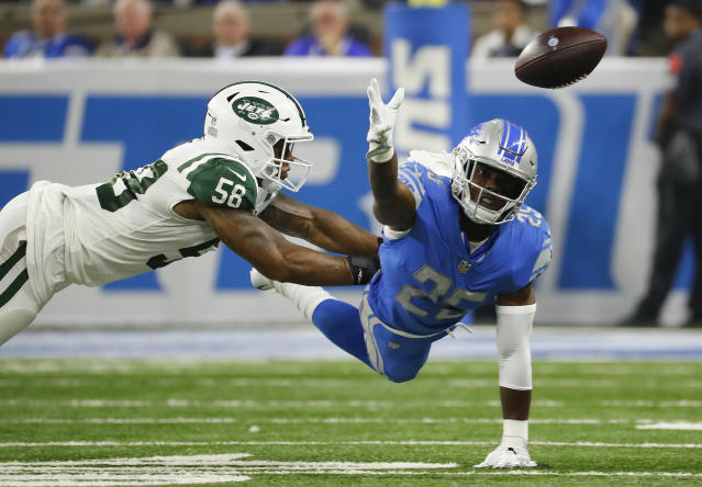 Detroit Lions running back Theo Riddick (25) reaches for the ball as New York Jets linebacker Kevin Pierre-Louis (56) defends in the first half of an NFL football game in Detroit, Monday, Sept. 10, 2018. (AP Photo/Rick Osentoski)