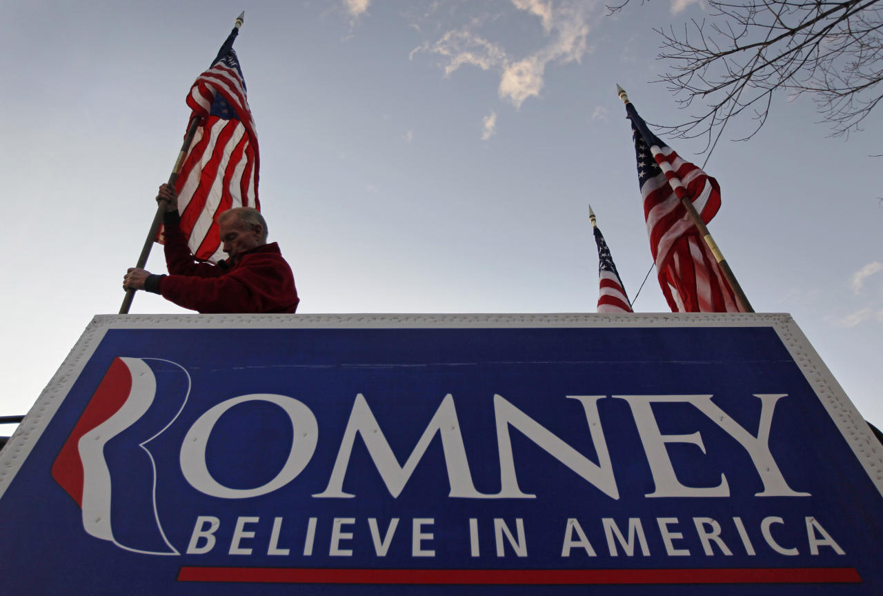 Jim Wilson of Buckingham,Va., mounts a flag onto his truck outside a scheduled campaign event for Republican presidential candidate, former Massachusetts Gov. Mitt Romney, at the Pinkerton Academy, Saturday, Jan. 7, 2012, in Derry, N.H. (AP Photo/Matt Rourke)