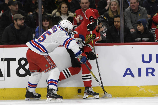 Chicago Blackhawks' Patrick Kane (88) battles New York Rangers' Ryan Lindgren (55) for a loose puck during the second period of an NHL hockey game Wednesday, Feb. 19, 2020, in Chicago. (AP Photo/Paul Beaty)