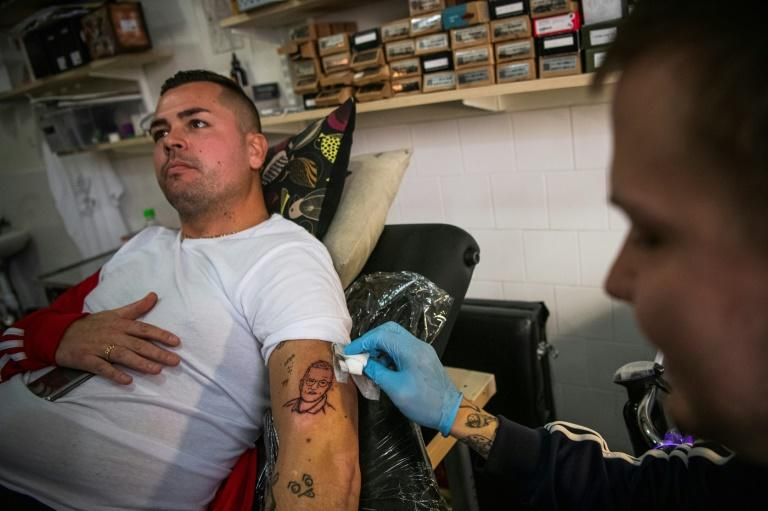 Zashay Tastas tattoos Gustav Lloyd Agerblad with the likeness of Sweden's star epidemiologist Anders Tegnell, who the coronavirus has turned into a household name (AFP Photo/Jonathan NACKSTRAND)