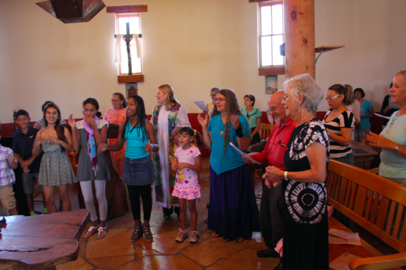 Rev. Alison Harrington (center, in white robe) leading her congregation in worship at Southside Presbyterian Church in Tucson, Arizona, in 2013.