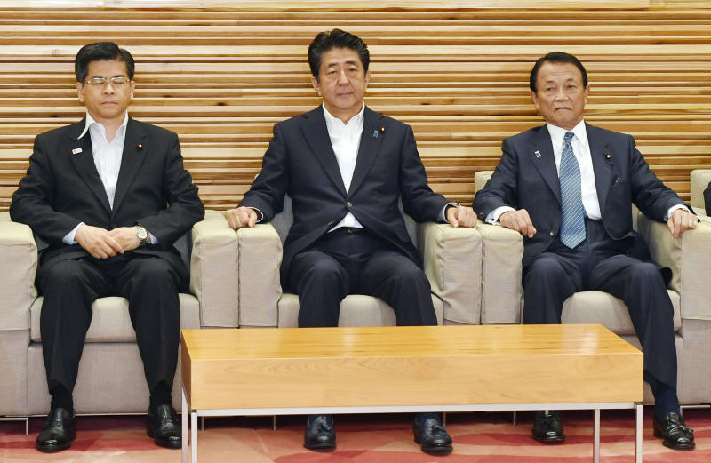 FILE - In this Aug. 2, 2019, file photo, Japan's Prime Minister Shinzo Abe, center, sits with Transport Minister Keiichi Ishii, left, and Finance Minister Taro Aso to attend a Cabinet meeting to decide to downgrade South Korea's trade status, in Tokyo. South Korea has threatened to end a military intelligence sharing agreement with Japan as their tensions escalate over export controls. The agreement, known as GSOMIA, is a symbol of the countries' trilateral security cooperation with their ally United States in the region. (Yoshitaka Sugawara/Kyodo News via AP, File)