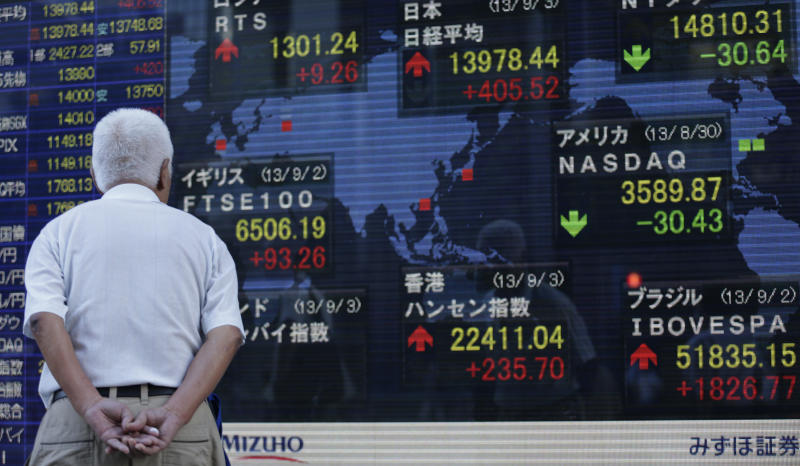 A man looks at an electronic stock indicator in Tokyo Tuesday, Sept. 3, 2013. Asian stock markets advanced Tuesday after the likelihood of an imminent U.S.-led attack against Syria faded and manufacturing rebounded in China and parts of Europe. Japan's benchmark Nikkei Index, top center, gained 405. 52 points, or 2.99 percent, to close at 13,978.44 while Hong Kong's Hang Seng, bottom center, jumped 235.70 points to 22,111.04. (AP Photo/Shizuo Kambayashi)