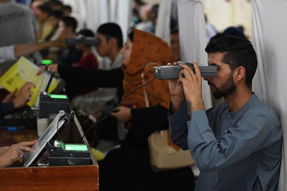 File: A man looks through an optical biometric reader to submit his passport application at an office in Kabul on 25 July 2021 (AFP via Getty Images)