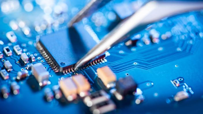 Electronic technician holding tweezers and assemblin a circuit board.