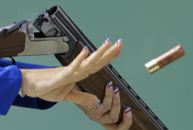France's Delphine Reau, her fingernails painted in the colors of the French flag, ejects a spent cartridge after shooting, during the women's trap final, at the 2012 Summer Olympics, Saturday, Aug. 4, 2012, in London. Reau took home the bronze.(AP Photo/Rebecca Blackwell)