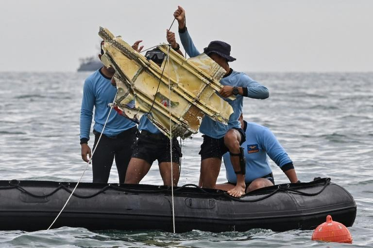 A piece of wreckage is pulled from the sea