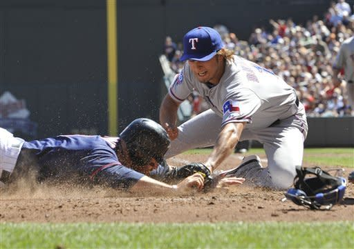 Texas Rangers pitcher Yu Darvish, covering the plate, tags out Minnesota Twins' Ryan Doumit, left, as he attempted to score on a runner's fielders choice in the fourth inning of a baseball game Saturday, April 14, 2012, in Minneapolis. (AP Photo/Jim Mone)