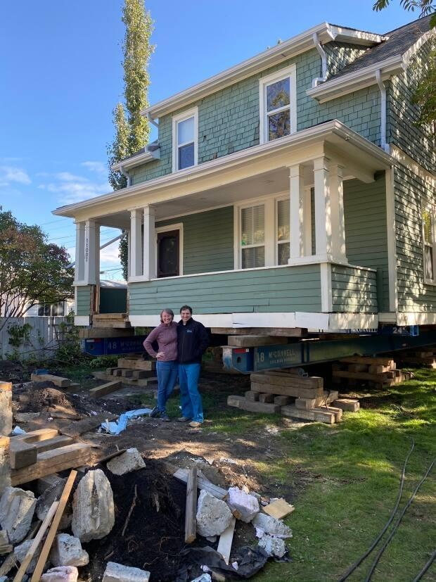 The Amrhein's stand in front of their home which was lifted off its original foundation in September 2020. A new foundation was poured, which will allow the house to continue to stand on its original lot.
