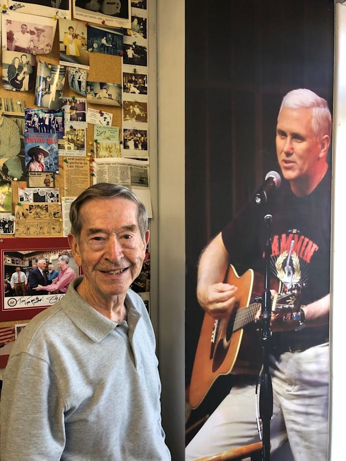 Tom Pickett at his Columbus, Ind., music shop next to a larger-than-life photo of Mike Pence playing guitar.