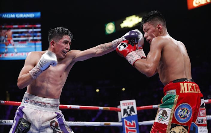 Leo Santa Cruz, left, jabs Miguel Flores during their WBA super featherweight title boxing match in November 2019.