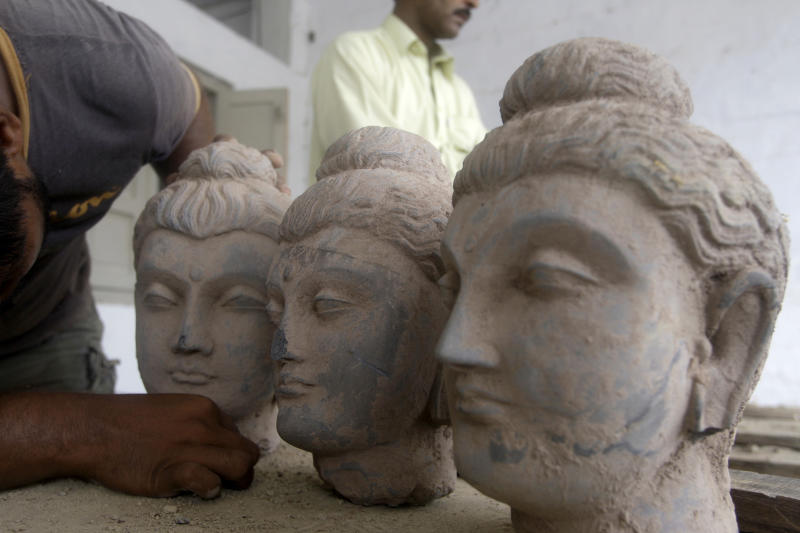 In this photo taken on July 6, 2012, A Pakistani official looks at Buddha statues confiscated by custom authorities in Karachi, Pakistan. Lacking the necessary cash and manpower, Pakistan is struggling to stem the flow of millions of dollars in ancient Buddhist artifacts that shadowy criminal gangs dig up from the country's northwest and smuggle to collectors around the world. (AP Photo/B.K. Shakil Adil)