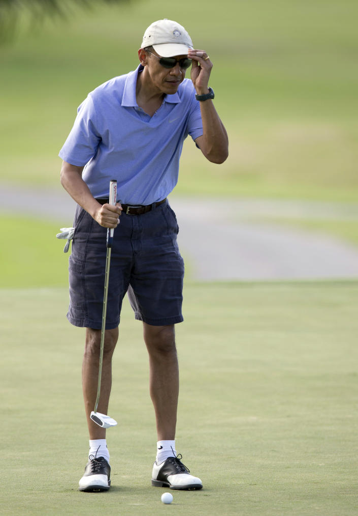 U.S. President Barack Obama adjusts his hat as he eyes his putt on the 18th green at Mid-Pacific County Club in Kailua, Hawaii, Monday, Dec. 23, 2013. The first family is in Hawaii for their annual holiday vacation. (AP Photo/Carolyn Kaster)