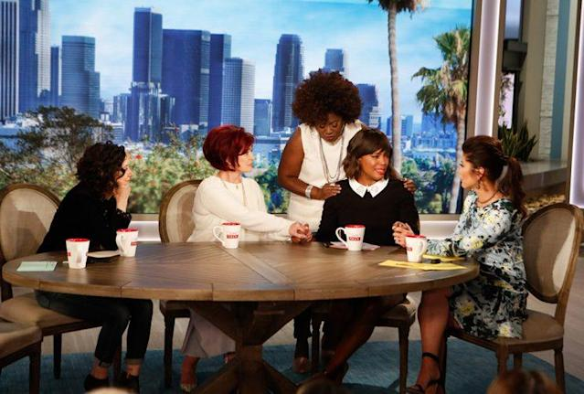 "The cast of ""The Talk"" after Aisha Tyler's announcement: From left, Sara Gilbert, Sharon Osbourne, Sheryl Underwood, Tyler, and Julie Chen. (Photo: Monty Brinton/CBS)"