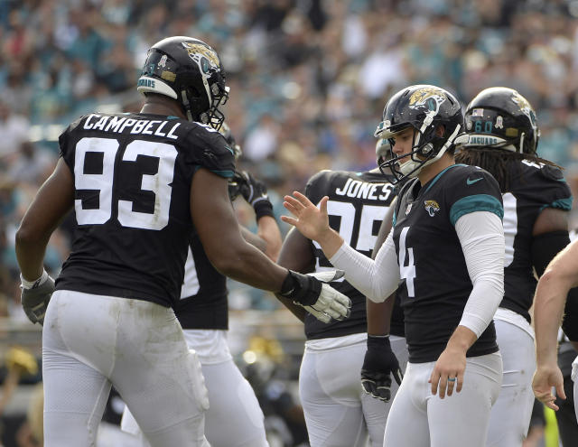 Jacksonville Jaguars kicker Josh Lambo (4) gets a hand shake from defensive end Calais Campbell (93) after kicking a field goal against the Indianapolis Colts during the first half of an NFL football game, Sunday, Dec. 2, 2018, in Jacksonville, Fla. (AP Photo/Phelan M. Ebenhack)