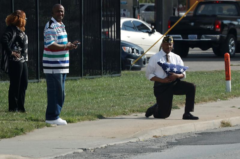 Marvin L. Boatright, as seen from President Donald Trump's motorcade, takes a knee while holding a folded American flag in Indianapolis, Indiana, on September 27, 2017. (Jonathan Ernst / Reuters)