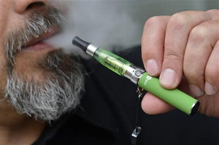 File of Gabor Kovacs of 'smoke no smoke' puffing on an e-cigarette that his shop sells at Camden in London