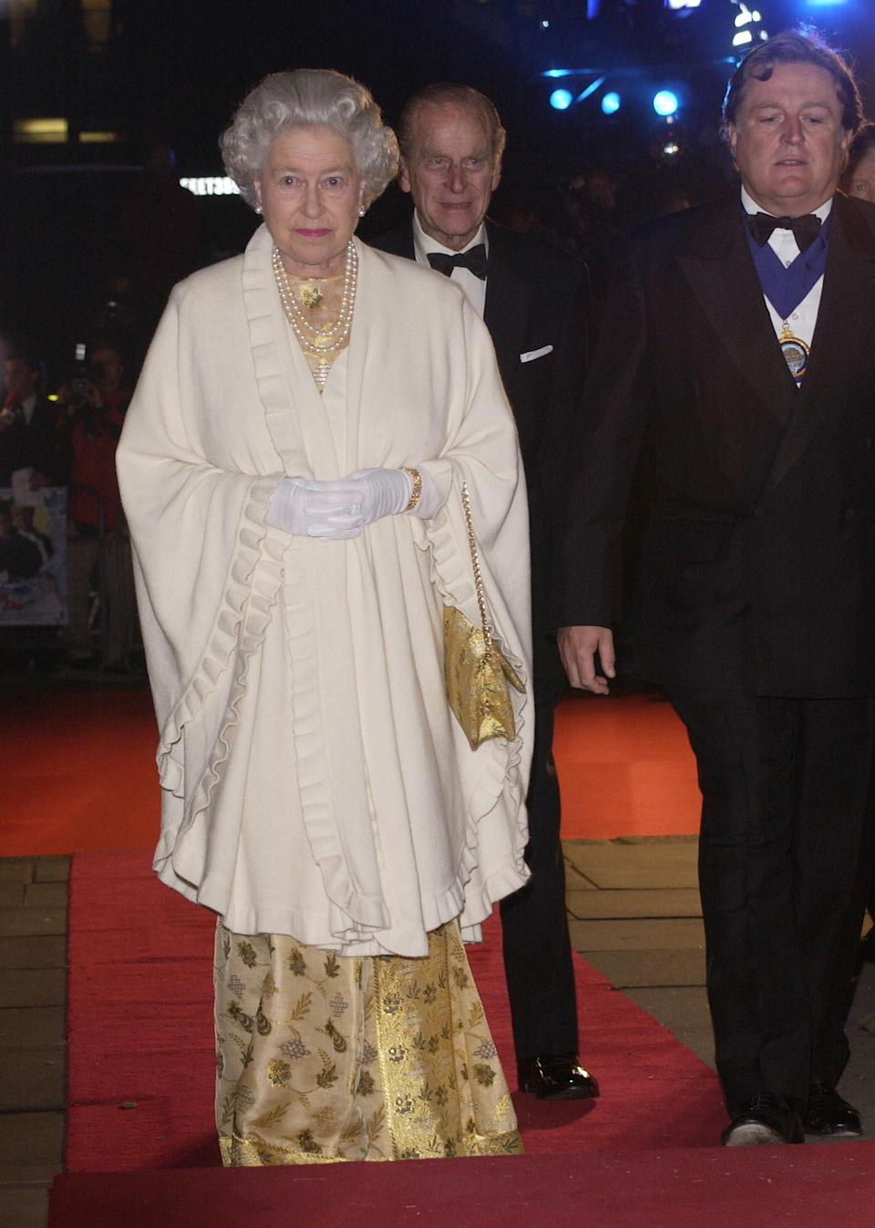 <p>Only the Queen can rock metallics, as the royal took to the red carpet back in 2002 wearing head-to-toe gold. <em>[Photo: Getty]</em> </p>