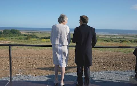 Theresa May and Emmanuel Macron take a moment to look out to sea in Normandy - Credit: PA
