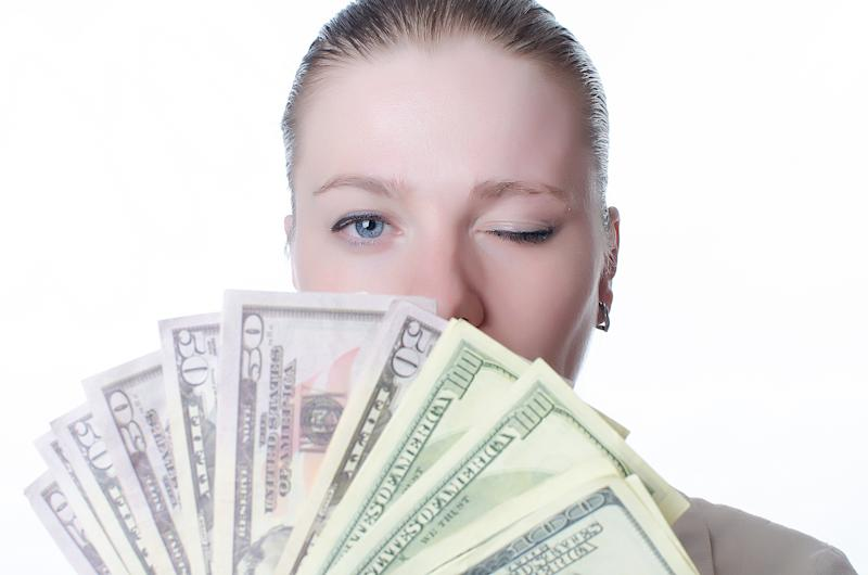 Young woman holding a lot of cash and winking