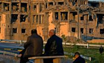 People sit in front of a Mosul building destroyed during fighting between Iraqi forces and IS jihadists in 2017