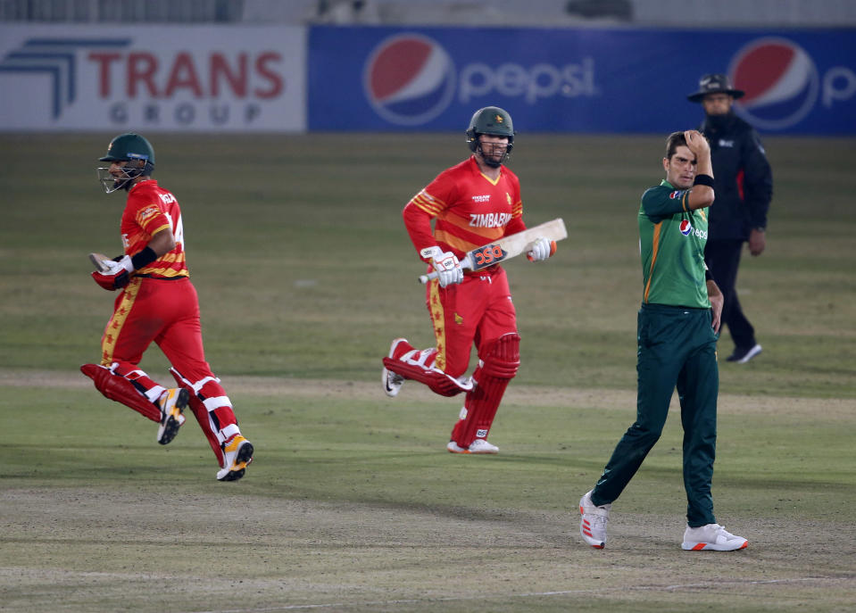 Zimbabwe's batsmen Sikandar Raza, left, and Brendan Taylor, center, take winning runs while Pakistani pacer Shaheen Shah, right, watches during the 3rd one-day international cricket match at the Pindi Cricket Stadium, in Rawalpindi, Pakistan, Tuesday, Nov. 3, 2020. (AP Photo/Anjum Naveed)