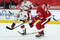 Carolina Hurricanes center Vincent Trocheck (16) loses his stick as he and Detroit Red Wings center Dylan Larkin (71) battle for the puck in the second period of an NHL hockey game Saturday, Jan. 16, 2021, in Detroit. (AP Photo/Paul Sancya)