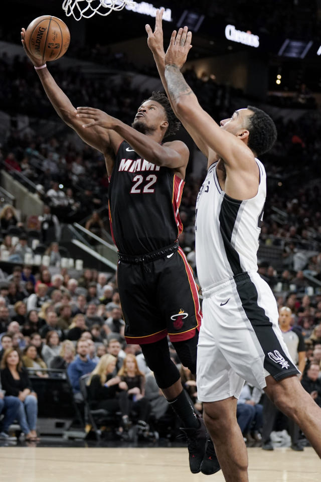 Miami Heat's Jimmy Butler (22) shoots against San Antonio Spurs' Trey Lyles during the first half of an NBA basketball game, Sunday, Jan. 19, 2020, in San Antonio. (AP Photo/Darren Abate)